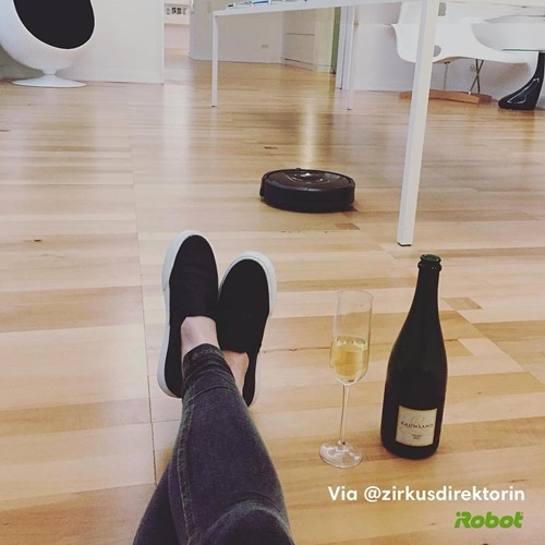 roomba cleaning with wine bottle and glass on floor